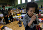 Kimiko Daigaku, 68, prays during a moment of silenceat the Wakabayashi Gym in Sendai on the one month anniversity of the earthquake and tsunami that hit Japan at 2:46 p.m. March 11, 2011. She is one of 320 evacuees living in the gym since their homes were destroyed in a 9.0 earthquake and tsunami. (The Press-Enterprise/ Mark Zaleski)