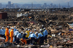 Sendai, Japan, firefighters and police officers sift through debris while searching for victims in the Arahama ward of Sendai in the Miyagi Prefecture of northern Japan.  (The Press-Enterprise/ Mark Zaleski)