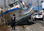 A woman walks past a fishing boat that washed ashore in Shichigahama, a fishing town of northern Sendai, Japan. (The Press-Enterprise/ Mark Zaleski)