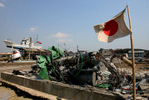 The Japanese flag is displayed as a fishing boat rests on top of a damaged building in Shichigahama, a fishing town of northern Sendai, Japan. (The Press-Enterprise/ Mark Zaleski)