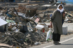 A woman carries supplies she bought at a convenience store miles away from her destroyed home in Shichigahama, a fishing town of northern Sendai, Japan. (The Press-Enterprise/ Mark Zaleski)