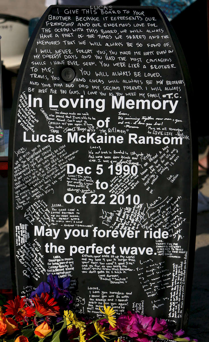 Family and friends signed a boogie board in memory of Lucas during a paddle-out memorial near the pier in Oceanside, Calif. (The Press-Enterprise/ Mark Zaleski)