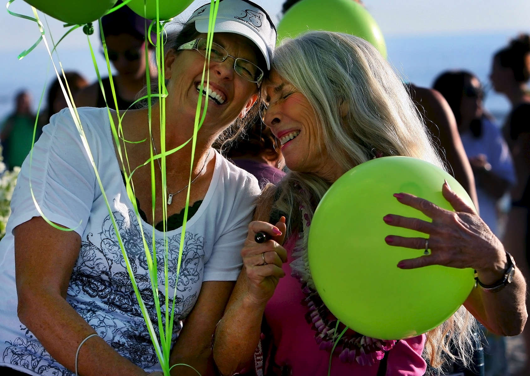 Candace Ransom shares a moment with her friend Linda Kirschner while writing the number 9 on a set of balloons in memory of her son Lucas Ransom before a paddle-out memorial near the Oceanside, Calif. pier. The number 9 was Lucas's water polo number at Perris High School in Riverside County. The UC Santa Barbara student was killed after being bitten by a shark while surfing with friends off the coast of  Santa Barbara. (The Press-Enterprise/ Mark Zaleski)