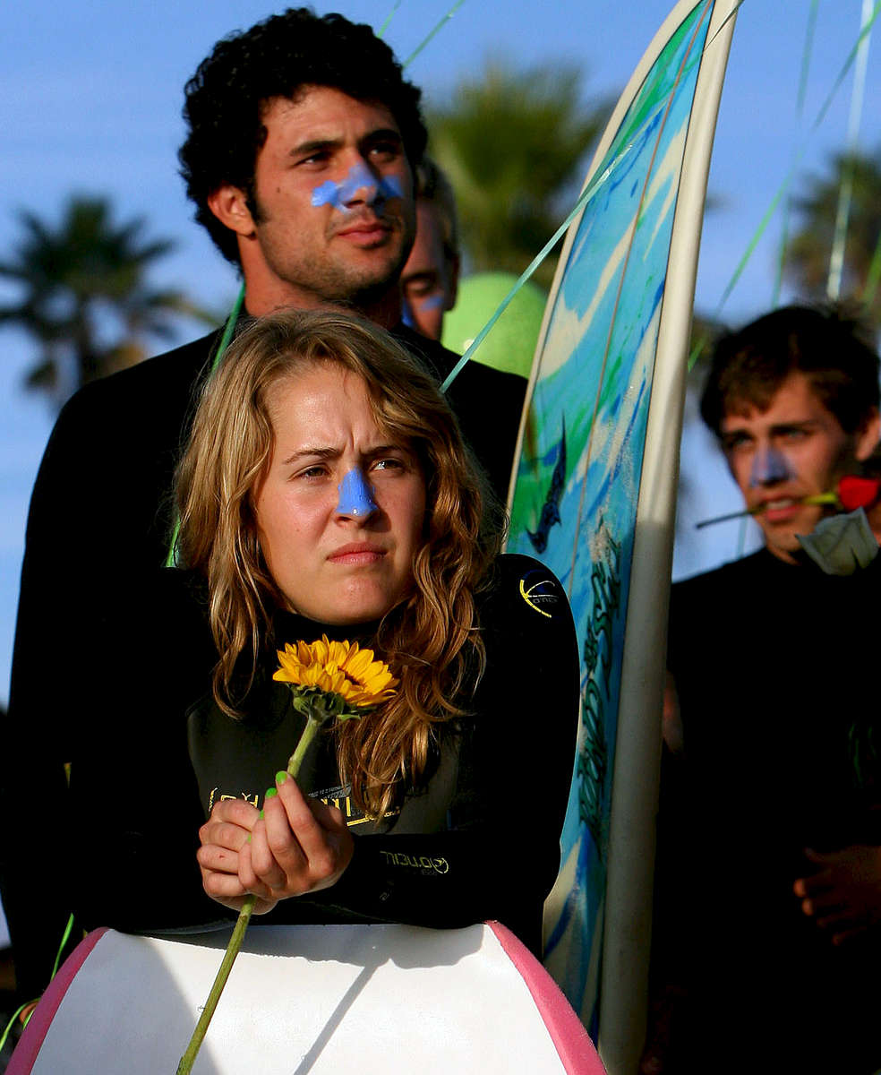 Friends of Lucas Ransom hold flowers while waitingfor the start of the paddle-out memorial near the Oceanside Pier. (The Press-Enterprise/ Mark Zaleski)