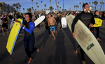 Body boarders and surfers run into the Pacific Ocean in memory of Lucas Ransom during a paddle-out memorial near the Oceanside Pier. (The Press-Enterprise/ Mark Zaleski)