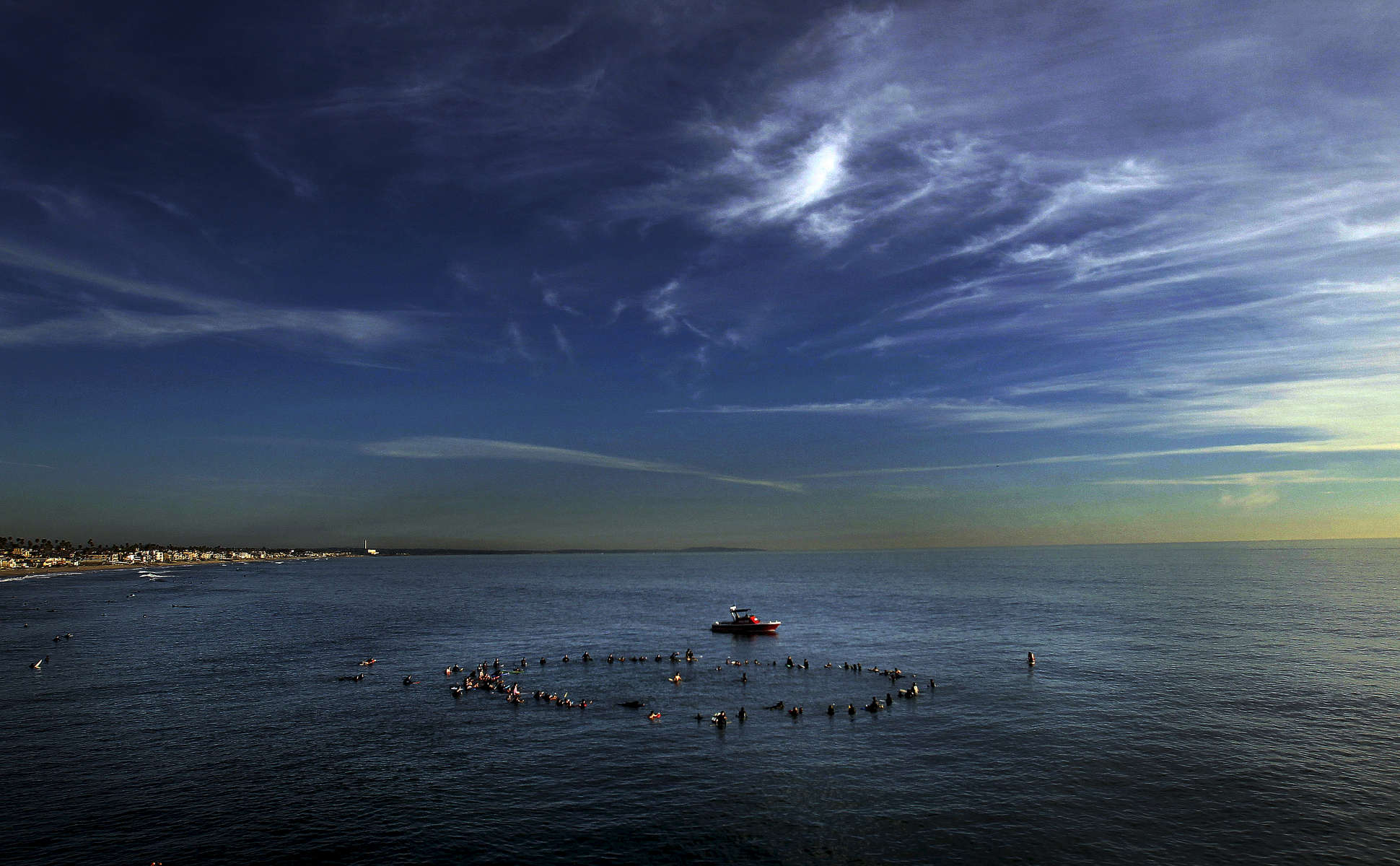 Family and friends gather around Travis Ransom, center, in the Pacific Ocean during a moment of silence in memory of his brother, Lucas Ransom, during a paddle-out memorial near the Oceanside Pier. (The Press-Enterprise/ Mark Zaleski)