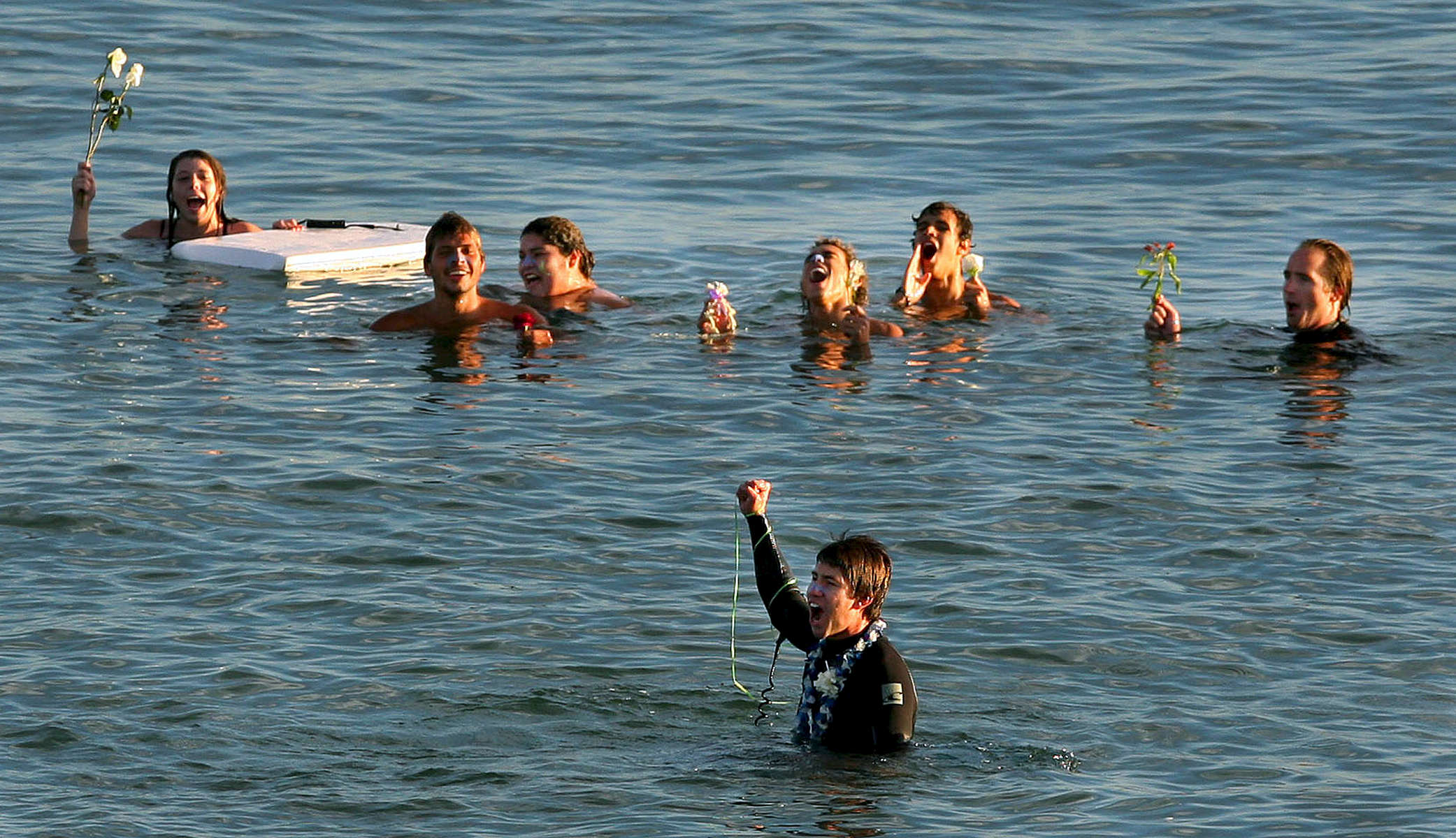 Family and friends gather near Travis Ransom, bottom, in the Pacific Ocean as they shout out Travis's brother name Lucas during a paddle-out memorial near the Oceanside Pier. (The Press-Enterprise/ Mark Zaleski)
