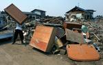 Shusuka Kikushi lifts a dresser onto a pile of damaged furniture while cleaning out his friend's destroyed homein Sendai, Japan. (The Press-Enterprise/ Mark Zaleski)