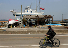 A man rides his bicycle past a fishing boat that landed on top of a building after a tsunami hit Shichigahama, a fishing town of northern Sendai, Japan. (The Press-Enterprise/ Mark Zaleski)