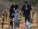 A man and his two daughters pray over a grave at a temporary burial site near a recycling centerin Higashimatsushima, a ward of Sendai, Japan. (The Press-Enterprise/ Mark Zaleski)
