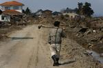 A man walks through the debris in his neighborhood in Sendai, in the Miyagi Prefecture of northern Japan. (The Press-Enterprise/ Mark Zaleski)