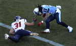 Tennessee Titans running back Chris Johnson scores a touchdown on an 11-yard run as Houston Texans free safety Shiloh Keo holds onto Johnson's hair in the third quarter of an NFL football game Sunday, Dec. 29, 2013, in Nashville, Tenn. (AP Photo/ Mark Zaleski)