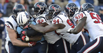 Tennessee Titans running back Chris Johnson is stoppedby Houston Texans defenders J.J. Watt, Earl Mitchell and Antonio Smith in the fourth quarter of an NFL football game on Dec. 29, 2013, in Nashville, Tenn. The Titans won 16-10. (AP Photo/ Mark Zaleski)