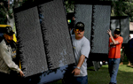 The Vietnam Veterans Memorial Moving Wall is a half-size replica of the memorial located in Washington, D.C., and travels the country honoring the dead and missing Americansfrom the Vietnam War (1959-1975). Volunteers carry several panels to put in place duringconstruction of The Moving Wall in Redlands, Calif. (The Press-Enterprise/ Mark Zaleski)