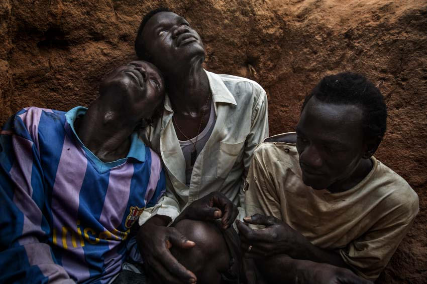 Africa, Sudan, South Kordofan. 8th dec 2013.  (from the left of the pic) Cucu Ahmed Turabi, 21, Saburi Hamid Juma, 25, Maw Tutu Grush, 28, take shelter in a foxhole between the Nuba Mountains and the Yida refugee camp, while an Antonov bomber of the Sudanese government flies over the area.Africa, Sudan, Kordofan Meridionale. 8 dicembre 2013. Dalla sinistra della foto: Ahmed Cucu Turabi, 21 anni, Juma Hamid Saburi, 25 anni, Maw Tutu Grush, 28 anni, cercano riparo in una trincea, tra i monti Nuba e il campo profughi di Yida, mentre un bombardiere Antonov del governo Sudanese sorvola la zona.