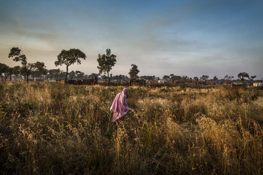 Africa, South Sudan, Unity State. 7th December 2013. Yida refugee camp in South Sudanese territory, 20 km far from the border with Sudan. The camp hosts 68,000 refugees from the Nuba Mountains. A woman walks through the fields. Africa, Sud Sudan, Unity State. 7 Dicembre 2013. Il Campo profughi di Yida in territorio Sud Sudanese, a 20 km dal confine con il Sudan. Il campo ospita 68.000 rifugiati dai Monti Nuba. Una donna cammina nei campi.
