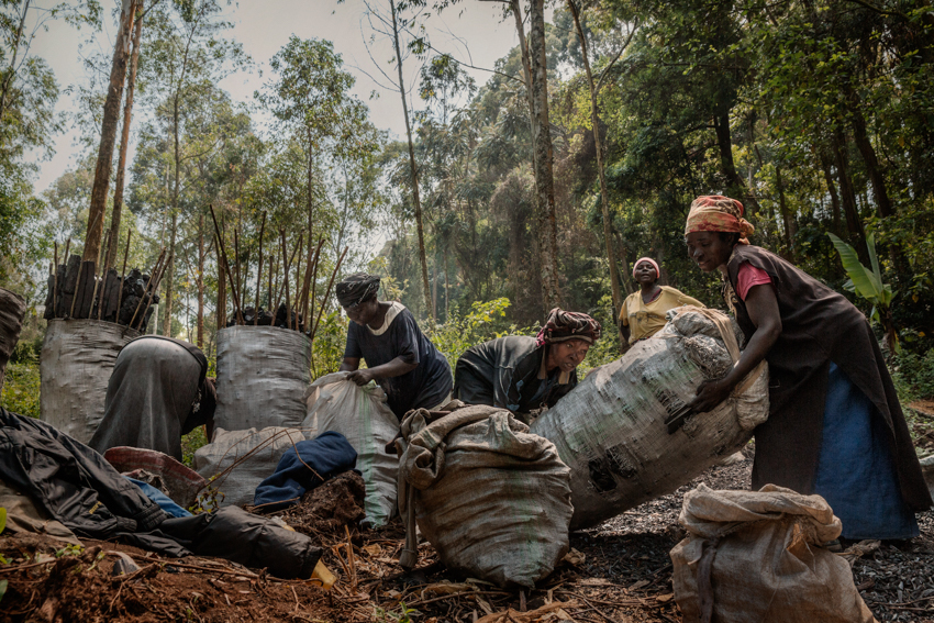Africa, Democratic Republic of Congo, South Kivu, Bukavu. 06/02/2017. A group of women working with coal. This is one of the numerous jobs done almost exclusively by women. After working the coal by hand, it is transported on their backs in bags that can weigh as much as 60 kg or more. These women carry the coal for kilometres up steep roads, from the forests to the nearest villages, and earn about two dollars a day.