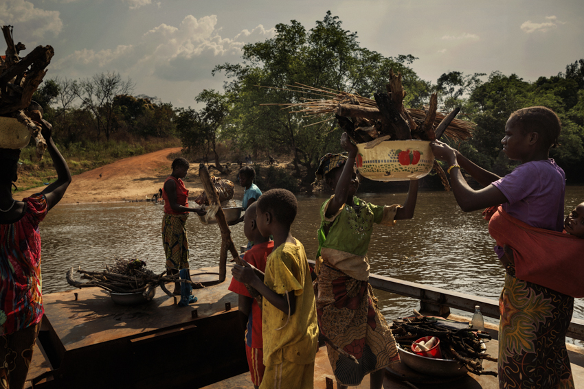 Africa, Central African Republic, Bambari. The road from Bambari to Ndassima is flanked by a succession of villages abandoned by the Christian population following the arrival of the Seleka rebels. There are visible traces of the looting and fires. A group of women crossing the water on a barge. 6th February 2015©Marco Gualazzini