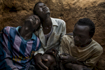Africa, Sudan, South Kordofan. 8th dec 2013.  (from the left of the pic) Cucu Ahmed Turabi, 21, Saburi Hamid Juma, 25, Maw Tutu Grush, 28, take shelter in a foxhole between the Nuba Mountains and the Yida refugee camp, while an Antonov bomber of the Sudanese government flies over the area. Sudan's army conducted an aerial campaign of destruction of property using Antonov Tranport planes adapted for bombing. Many witnesses also report the use cluster bombs, looting and house to house killing, randomly targeting the Nuban and pro-SPLA-N supporters across South Kordofan.