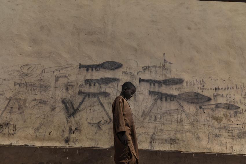 """Africa, Chad, 13th October 2018. Orphaned children, mainly Nigerian refugees, live together as a group in the Koran schools. During the day, they go begging and are known as Almajiri. These children, who live in the Lake Chad basin, are growing up in a constant situation of war, and all they've ever known is the weapons and deaths they draw on the walls of the city.  Almajiri is gotten from an Arabic word {quote}Al-Muhajirun{quote} which can be translated to mean a person who leaves his home in search of Islamic knowledgeAfrica, Ciad, 13 Ottobre 2018. Bambini orfani, prevalentemente rifugiati Nigeriani, vivono collettivamente all'interno delle scuole coraniche, e durante la giornata mendicano e sono chiamati Almajiri. Questi bambini che vivono nel bacino del lago Chad crescono in una costante situazione di guerra, e la loro unica realtà è fatta di armi e morti che disegnano sui muri della città.  Almajiri deriva dalla parola arabo e significa """"Al-Muhajirun{quote} e può essere tradotto con: una persona che lascia la propria casa, alla ricerca delle conoscenza Islamica."""