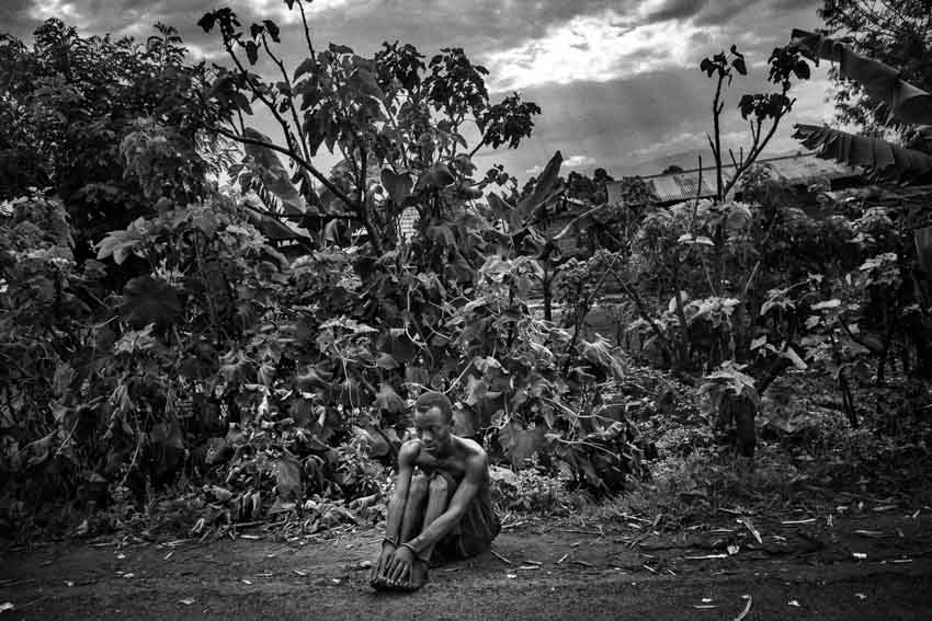 Africa, R.D.C.- North Kivu, Rutshuru. A view of the territory of the Province of Rutshuru, governed by the M23 rebels, successors of the CNDP and accused by both the UN and the government of Kinshasa of being supported by Rwanda. A mentally ill kid chained is sitting on the edge of the road. He has been shackled by his parents, because he used to throws rocks against M23\'s vehicles. 16th October 2012.©Marco Gualazzini/Getty Images Grants for Editorial Photography Recipient 2013.