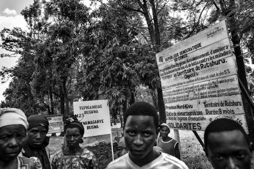 """Africa, R.D.C.- North Kivu, Rutshuru. A group of refugees are seen in the territory of the Province of Rutshuru, governed by the M23 rebels, successors of the CNDP and accused by both the UN and the government of Kinshasa of being supported by Rwanda. The signboard on the background has the notice: """"Territory governed by the M23. Here the corruption is banned."""". 16th October 2012.©Marco Gualazzini/Getty Images Grants for Editorial Photography Recipient 2013."""