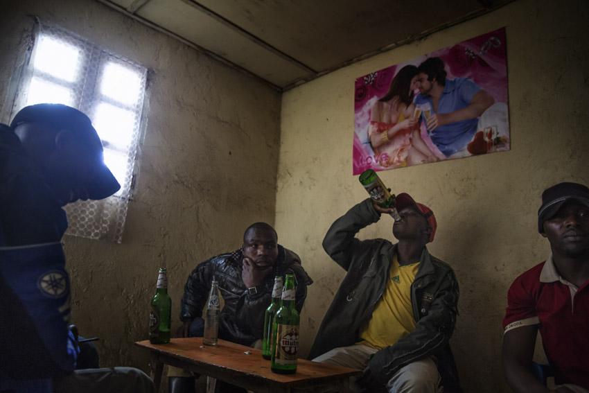 Republic Democratic of Congo, North Kivu, Masisi, Rubaya. 20/09/2013. Rubaya, in the region of Masisi in North Kivu, grew up around the mining and extraction of coltan and manganite. The city, a heap of wooden shacks that has formed on the sides of a single muddy road, is under the rigid control of the Nyatura, Congolese Hutu soldiers allied with the FARDC, the regular armed forces.  A dailylife scene. Some men sit in a brothel drinking beers.Repubblica Democratica del Congo, Nord Kivu, Masisi, Rubaya. 20/09/2013. Rubaya, nella regione del Masisi in nord Kivu, si è sviluppata intorno all\'attività mineraria di estrazione della manganite e del Coltan. La città, un cumulo di baracche in legno cresciute ai lati di un\'unica strada di fango, è sotto il rigido controllo dei Nyatura, militari hutu congolesi alleati con le FARDC, le forze armate regolari. Una scena di vita quotidiana. Un gruppo di uomini siede in un bordello a bere birra.