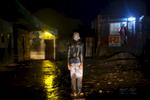 Republic Democratic of Congo, North Kivu, Masisi, Rubaya. 19/09/2013. Rubaya, in the region of Masisi in North Kivu, grew up around the mining and extraction of coltan and manganite. The city, a heap of wooden shacks that has formed on the sides of a single muddy road, is under the rigid control of the Nyatura, Congolese Hutu soldiers allied with the FARDC, the regular armed forces. A drunk man at attention in front of the police station. Repubblica Democratica del Congo, Nord Kivu, Masisi, Rubaya. 19/09/2013. Rubaya, nella regione del Masisi in nord Kivu, si è sviluppata intorno all\'attività mineraria di estrazione della manganite e del Coltan. La città, un cumulo di baracche in legno cresciute ai lati di un\'unica strada di fango, è sotto il rigido controllo dei Nyatura, militari hutu congolesi alleati con le FARDC, le forze armate regolari. Un ubbriaco sull'attenti davanti alla stazione di polizia.
