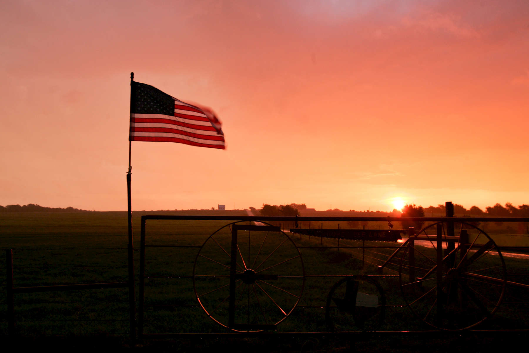 Sunrise in the rain at Prairie Chapel road. American flag.