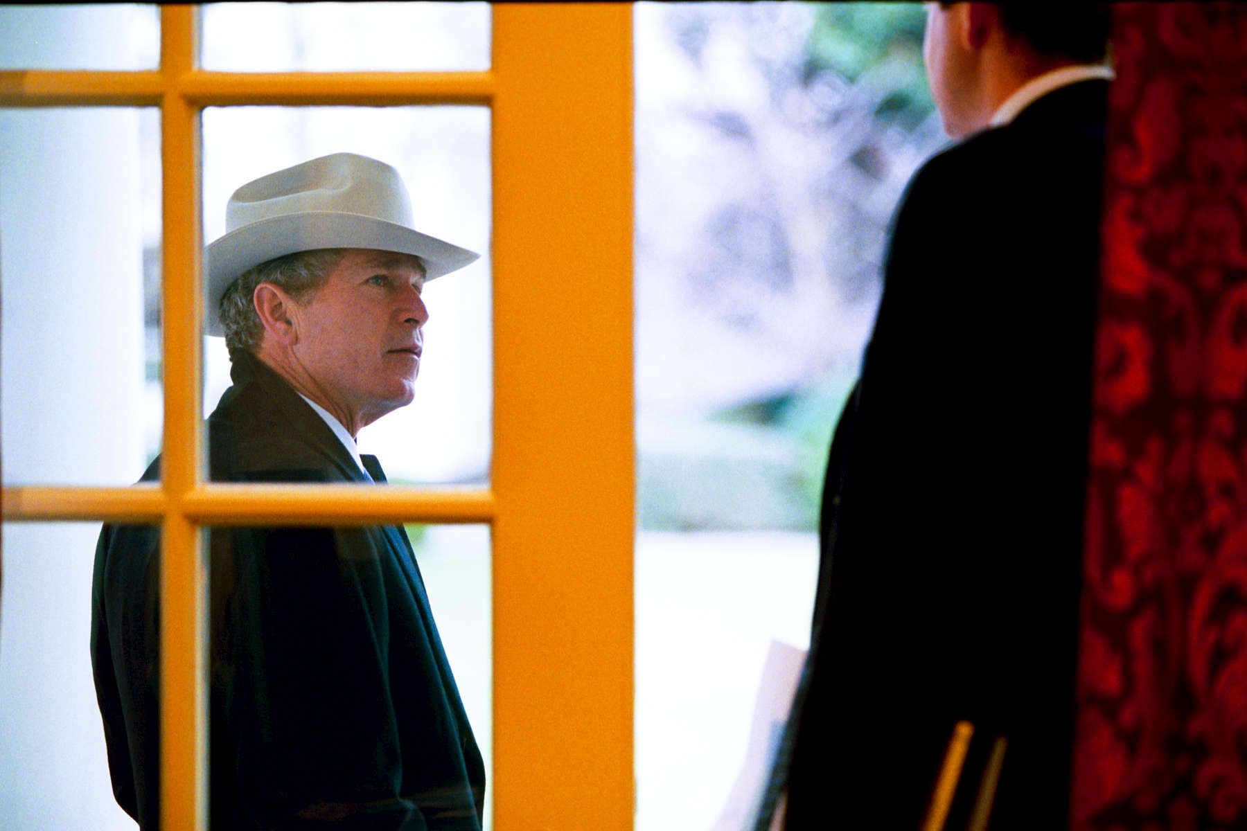 President Bush stands on the Colonnade and talks with Dan Bartlett who is standing in the doorway to the Outer Oval Office. The President is wearing a coat and cowboy hat.