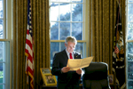 President Bush stands at his desk and reads a file between Meetings with Republican Members of the Senate. Oval Office. POW