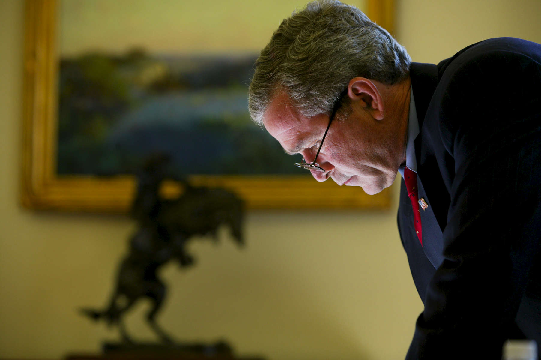 President Bush in the Oval Office following the meeting with President Mikhail Saakashvili of Georgia. Tight shot of President Bush writing at his desk. {quote}The Bronco Buster{quote} sculpture by Frederic Remington is pictured. Bush Family Scrapbook February 17 - March 9, 2004