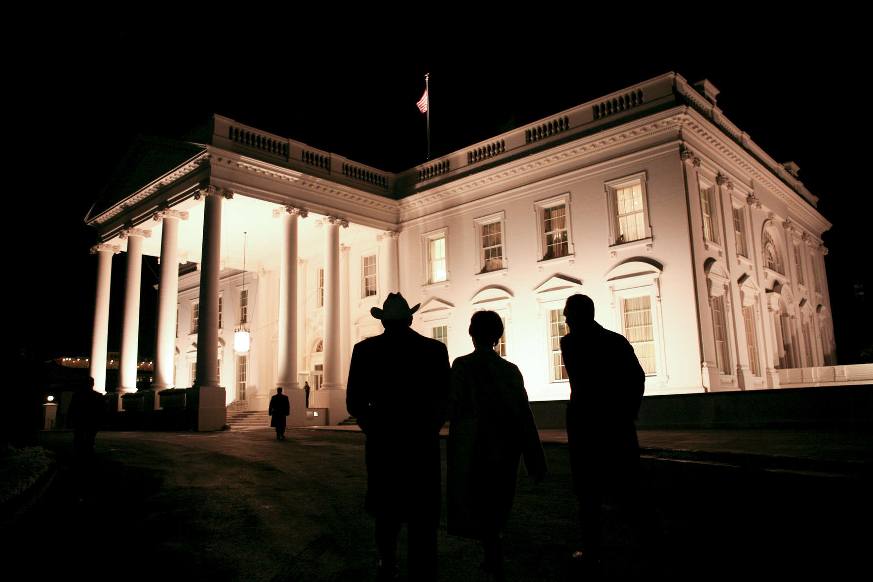 President Bush, Laura Bush: Departure following Reception in Honor of the Chief of Protocol Ambassador Donald Ensenat at Blair House. Walking down Pennsylvania Avenue to the North Grounds of the White House.  Silhouette. POW