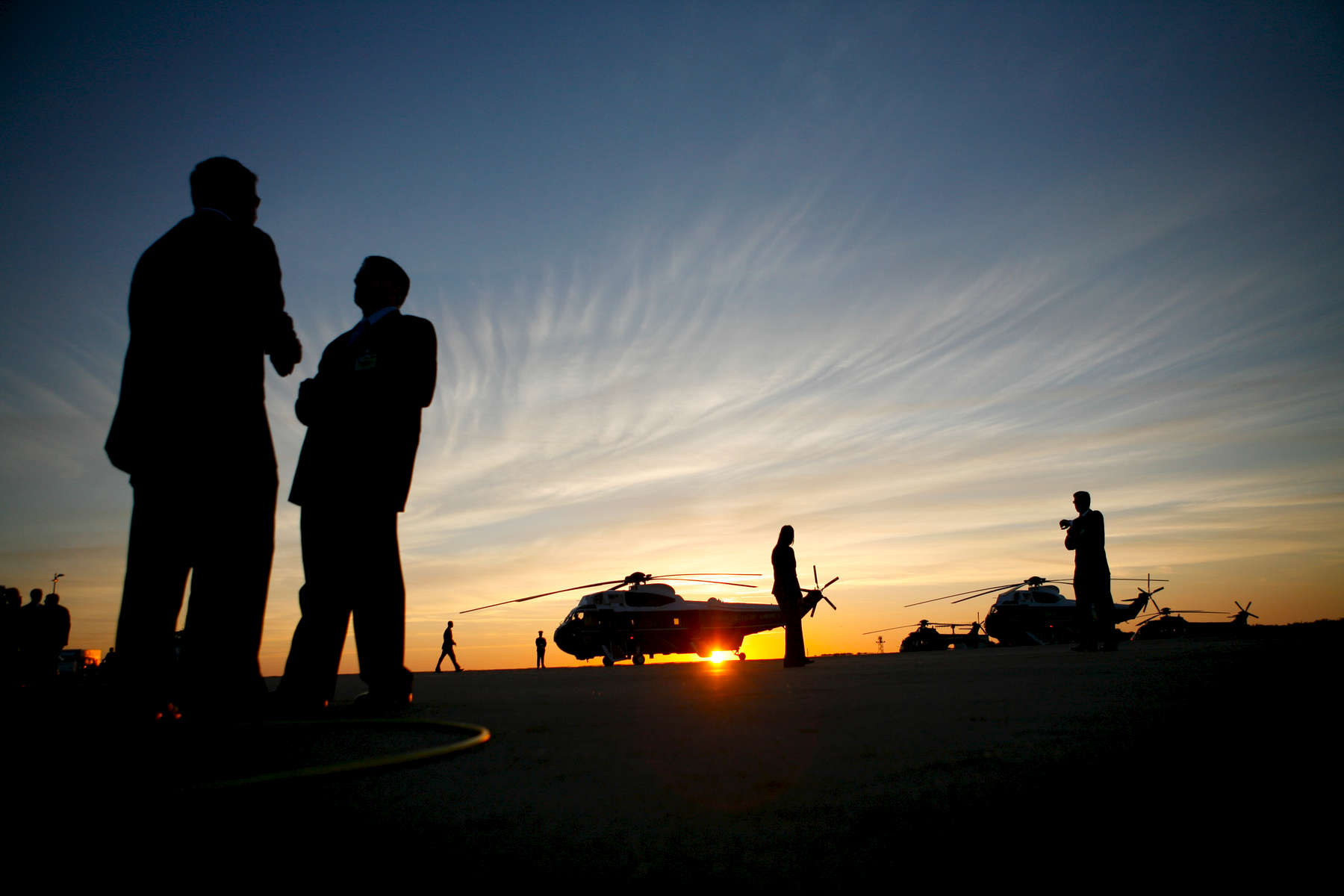 President Bush, Laura Bush: Arrival at Rostock - Laage Airport. Rostock, Germany. Marine One at sunset. Silhouette of staff members.