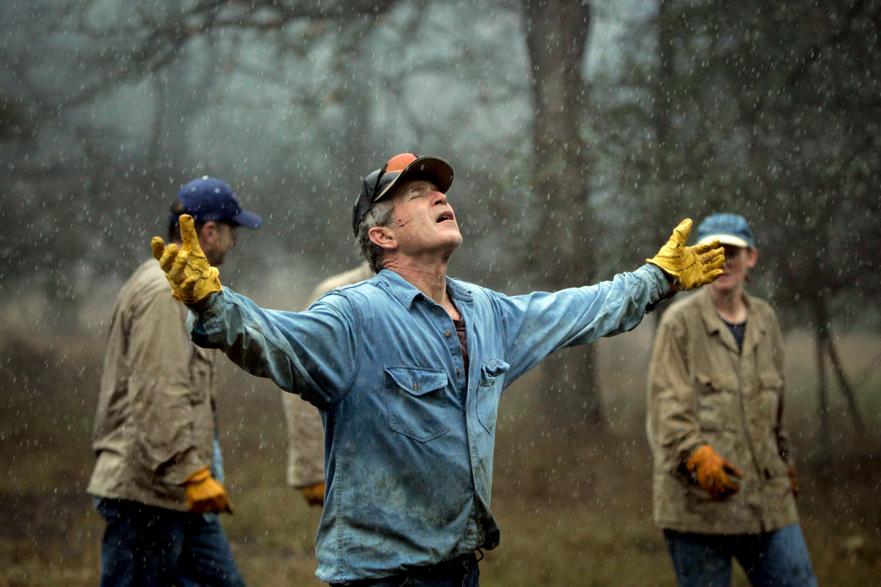 President Bush: Brush clearing and burning with staff. Ranch, Crawford, Texas. The President holds his arms out in the rain.