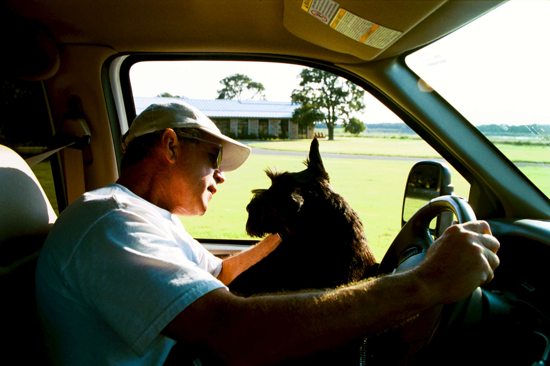 President Bush drives his truck at the Ranch. Barney sits in his lap. Crawford, Texas. Restricted. Do not print without approval.  Bush Family Scrapbook August 1-August 27, 2003