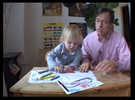 child and man at table drawingThe Genius Maker is work-in-progress, edited from footage shot over a period of 5 years. a vision of what can happen when parents get overly invested in their child's success in our increasingly competitive educational system. Joe Gibbons plays Dr. Baldwin the self-styled child education expert eager to put his unorthodox theories into practice. In Rumplestiltskin fashion, he manages to convince a pregnant couple that by allowing him to coach their daughter from birth, he can guarantee her acceptance into a coveted {quote}gifted-only{quote} kindergarden program.Dr. Baldwin documents his lessons with the young Zoe as proof that {quote}geniuses are not born, but made.{quote} What gets recorded over the next five years is his growing desperation for success and Zoe's growing indifference to it.Directed & Edited by Emily Breer; Performed, Shot and Recorded by Joe Gibbons