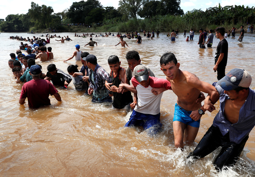 Migrants, part of a caravan traveling to the U.S., make a human chain to pull people from the Suchiate river that separates Guatemala and Mexico in Ciudad Hidalgo in Mexico.