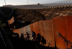 Migrants, part of a caravan of thousands from Central America trying to reach the United States, climb down a steep hill after giving up on trying to climb the border wall into the U.S. from Tijuana, Mexico.