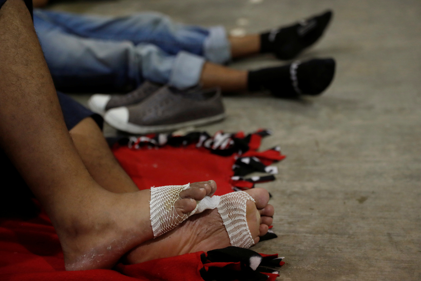 Migrants, part of a caravan traveling to the U.S., rest with bandaged feet in a gym after arriving in Mapastepec, Mexico.
