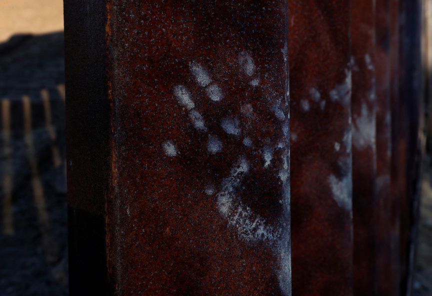 Hand prints from dirt and mud are seen on the border fence in Tijuana, Mexico.