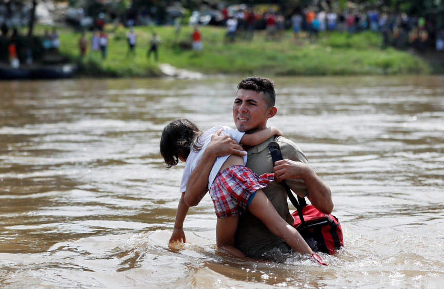 A man clutches on to a child, both of them members of a caravan traveling to the U.S., as he struggles to cross the Suchiate river from Guatemala to Mexico in Ciudad Hidalgo.