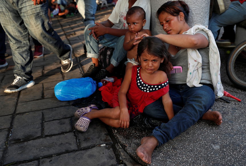 Young migrant Zuria Castro, 4, cries silent tears as her mother Joselyn Castellanos brushes her hair while her brother Mateo Castellanos, 10 months, plays nearby as they rest in the middle of the Central Park of Miguel Hidalgo in Tapachula, Mexico.