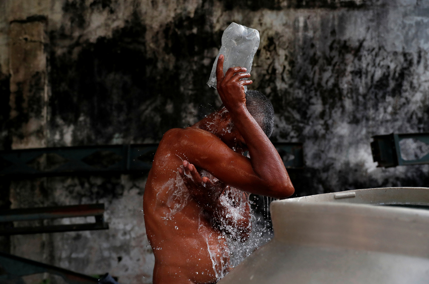 Jose Angel Salinas of Honduras bathes near a park as his fellow migrants, part of a caravan traveling to the U.S., rest in the park in Huixtla, Mexico.