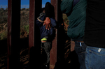 A Honduran migrant from the caravan of Central American migrants, pulls a young boy through the border fence into the U.S. as other Hondurans scale the fence from Tijuana, Mexico to seek asylum.