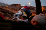Honduran migrants, part of a caravan of migrants from Central America traveling with the intention of reaching the U.S. jump over a border fence into the U.S. from Tijuana, Mexico December 14, 2018. REUTERS/Leah Millis