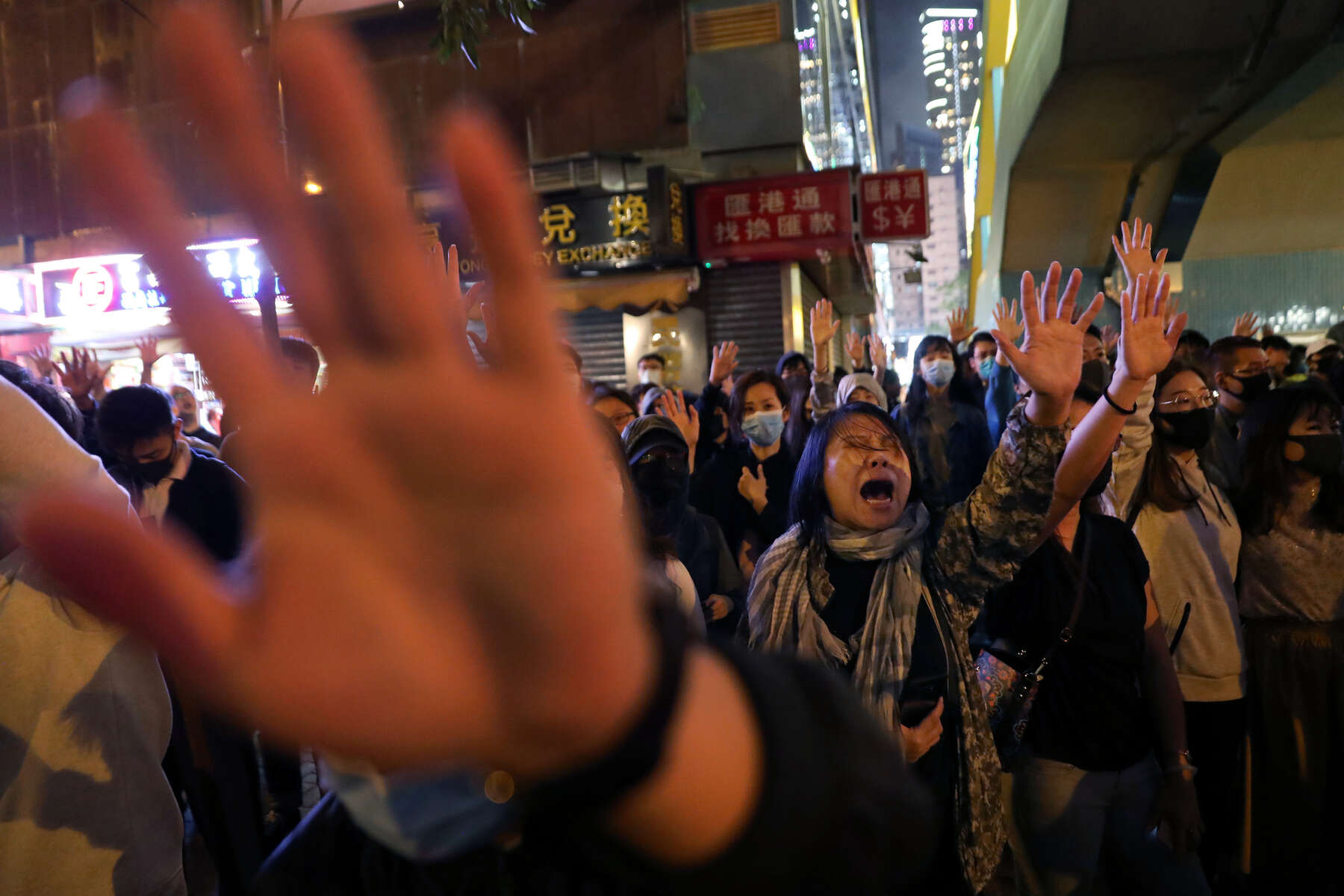 Protesters sing Glory to Hong Kong and hold up their hands to signify the {quote}five demands{quote} outside of Polytechnic University (PolyU) while police keep it under siege in Hong Kong, China, November 25, 2019.