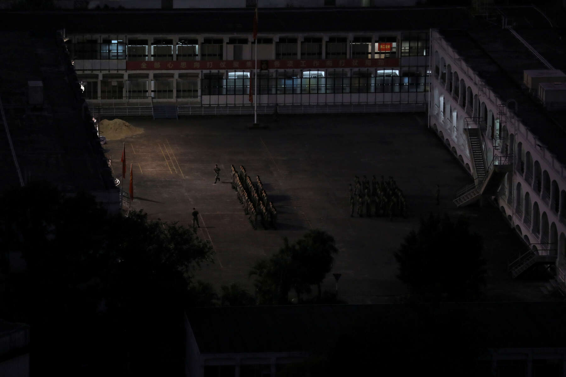 People's Liberation Army (PLA) soldiers stand in formation next to Hong Kong Polytechnic University (PolyU), Hong Kong, China November 23, 2019. The barracks where the PLA soldiers are housed, where they train and stay fit is located across the street from the University. There was a constant fear that the mainland Chinese government might send in military, risking reliving something like the Tiananmen Square massacre.