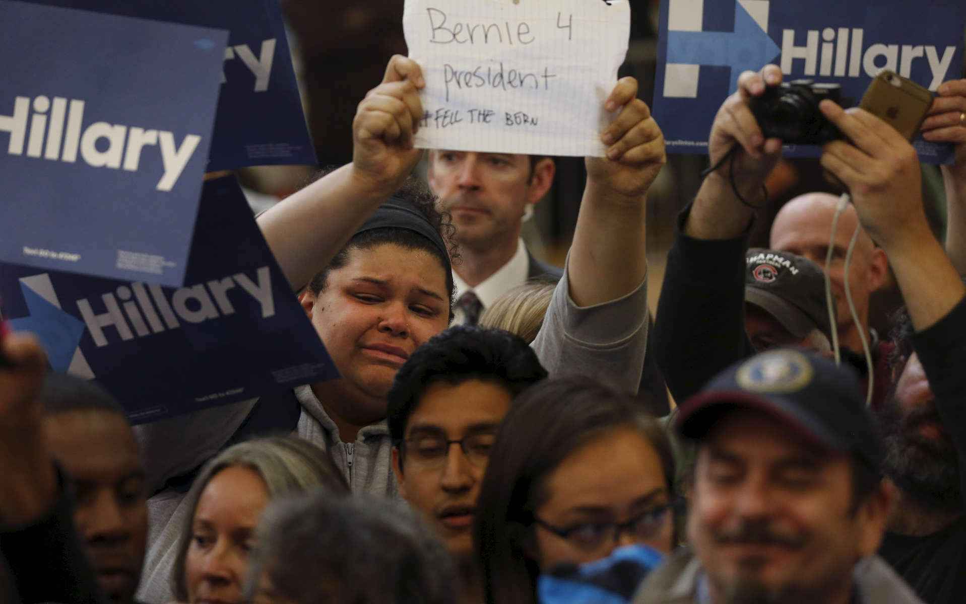 A supporter of presidential candidate Bernie Sanders cries as she holds up a sign while presidential candidate Hillary Clinton greets supporters at a campaign rally at La Escuelita Elementary School May 6, 2016 in Oakland, Calif.
