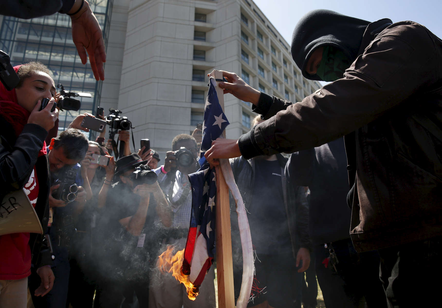 A protester burns a flag that was ripped from a Donald Trump supporter in front of a wall of media outside of the Hyatt Regency during the first day of the California Republican Party Convention which featured speeches from Presidential candidates Donald Trump and John Kasich among others April 29, 2016 in Burlingame, Calif.